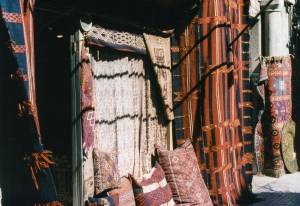 A rug shop with wares typically displayed on every available surface.